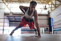 Female boxer looking at camera while exercising in boxing ring at fitness center. Strong female fighter in boxing gym training hard. — Stock Photo