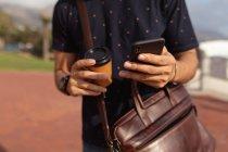 Vista frontale metà sezione dell'uomo che indossa una borsa a tracolla, con in mano un caffè da asporto e utilizzando uno smartphone all'aperto al sole — Foto stock