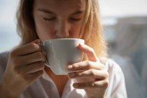 Vista frontal de perto de uma jovem caucasiana vestindo uma camisa branca bebendo café com os olhos fechados . — Fotografia de Stock