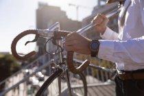 Vue latérale de la partie médiane de l'homme portant son vélo descendant les marches de la ville au soleil. Nomade numérique en mouvement . — Photo de stock