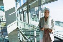 Mujer de negocios feliz en hiyab mirando la cámara mientras trabaja en la tableta digital cerca de la barandilla en la oficina. - foto de stock
