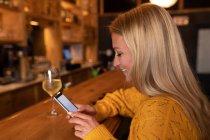 Vue latérale d'une jeune femme caucasienne heureuse se détendant en vacances dans un bar, buvant du vin et utilisant un smartphone — Photo de stock