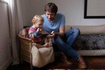 Вид спереди на молодого кавказского отца и его ребенка с помощью смартфона — стоковое фото