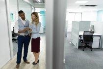 Vista frontal de uma jovem caucasiana e um jovem afro-americano de pé e usando um computador tablet juntos no corredor de um escritório moderno, com a porta de um escritório vazio em primeiro plano — Fotografia de Stock