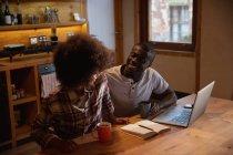 Vista elevada de un joven afroamericano sonriente y una joven mestiza hablando, tomando café y usando una computadora portátil sentada en la mesa de su cocina en casa - foto de stock