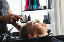Side view close up of hairdresser and a young Caucasian woman having her hair washed in a hair salon — Stock Photo