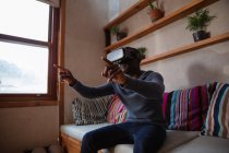 Side view close up of a young African American man wearing a VR headset sitting on a sofa at home, with his arms raised and fingers pointing — Stock Photo