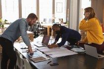 Vista laterale di un giovane afroamericano e di un giovane caucasico in piedi e appoggiato a una scrivania che lavorano insieme a una collega caucasica seduta su una scrivania in un ufficio creativo — Foto stock
