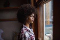 Vista lateral close-up de uma jovem mulher de raça mista vestindo uma camisa marcada em pé por uma janela em casa olhando para fora — Fotografia de Stock