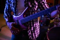 Передній вид людини, що грає на електричній бас-гітарі під час сесії в студії звукозапису. — стокове фото