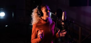 Side view of a young Caucasian female singer wearing headphones and singing in front of a microphone in a recording studio, gesturing and with her eyes closed — Stock Photo