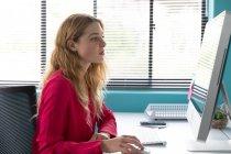 Vista lateral fechar uma jovem mulher caucasiana sentada em uma mesa por uma janela usando um computador no escritório moderno de um negócio criativo — Fotografia de Stock