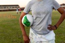 Vista frontal parte média do jogador de rugby feminino em pé em um campo esportivo com a mão no quadril, segurando uma bola de rugby sob o braço durante uma sessão de treinamento — Fotografia de Stock