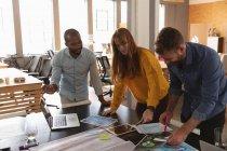 Vista frontale da vicino di un giovane uomo afroamericano e di un giovane uomo e donna caucasici in piedi e appoggiati a una scrivania che lavorano insieme a un progetto in un ufficio creativo — Foto stock