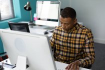 Front view of a young African American man sitting at a desk using a computer in the modern office of a creative business, with an empty workstation in the background — Stock Photo