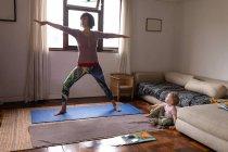 Vista frontal de uma jovem mãe caucasiana em uma pose de ioga ao lado de seu bebê — Fotografia de Stock