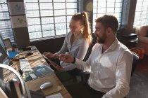 Vue latérale surélevée d'une jeune femme caucasienne et d'un homme assis à un bureau souriant en regardant une tablette dans un bureau créatif — Photo de stock