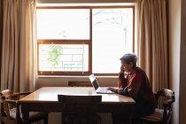 Вид сбоку пожилой белой женщины, сидящей дома за столом и делающей телефонный звонок и ноутбук — стоковое фото