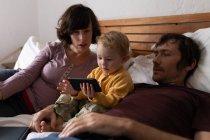 Vista lateral de cerca de un joven padre y madre caucásicos acostados en una cama mientras su bebé sostiene un teléfono inteligente - foto de stock