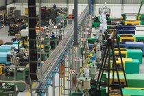 High angle view of factory workers operating machines in a warehouse at a factory processing plant — Stock Photo