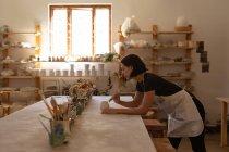 Вид сбоку на молодую кавказскую горшечницу, прислонившуюся к рабочему столу и остекленную кастрюлю в керамической мастерской — стоковое фото