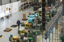 Вид сбоку на молодого афроамериканца, осматривающего оборудование на складе на заводе — стоковое фото