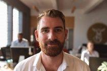 Retrato close-up de um jovem caucasiano com cabelo curto e barba olhando para a câmera sorrindo em um escritório criativo, com colegas trabalhando em mesas no fundo — Fotografia de Stock