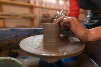 Вид збоку крупним планом рук жіночий Поттер формування мокрій глини в каструлю форму на гончарних колесо в гончарної студії — стокове фото