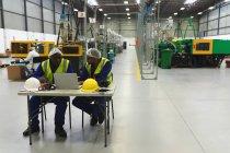Vue de devant d'un ouvrier d'usine métis d'âge moyen portant des lunettes et d'un ouvrier d'usine afro-américain Yong assis à une table et utilisant un ordinateur portable dans un entrepôt d'une usine de transformation — Photo de stock