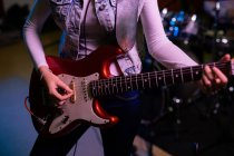 Передній вид жінки, що грає на електрогітарі під час сесії в студії звукозапису. — стокове фото