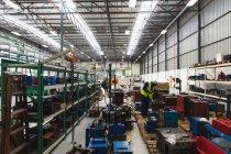 Vista lateral de um jovem trabalhador da fábrica afro-americano que inspeciona equipamentos em uma área de armazenamento em um armazém em uma fábrica de processamento, com prateleiras de peças e equipamentos em segundo plano — Fotografia de Stock