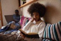 Вид спереди молодая женщина смешанной расы, сидящая на диване и читающая книгу дома, ее партнер, молодой афроамериканец, сидит на диване, используя ноутбук на заднем плане . — стоковое фото