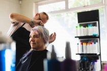 Передній вигляд середнього віку Кавказький самець перукаря і молода кавказька жінка, що стилізована в салоні для волосся. — стокове фото