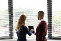 Rückseite Nahaufnahme eines jungen afrikanisch-amerikanischen Mannes und einer jungen kaukasischen Frau, die vor einem Fenster stehen und gemeinsam im Büro eines Kreativunternehmens auf einen Tablet-Computer schauen — Stockfoto