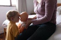 Vista lateral en la parte media de una joven madre caucásica que tiene una muñeca frente a su bebé - foto de stock
