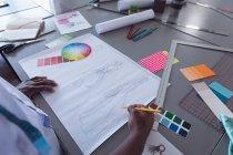 Вид через плечо студентки моды, работающей над дизайном в студии колледжа моды — стоковое фото