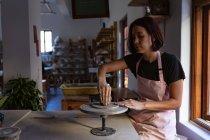 Вид сбоку на молодую кавказскую гончарку, сидящую за рабочим столом, работающую с глиной на бандинговом колесе в керамической мастерской — стоковое фото