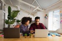 Frontansicht eines jungen Mannes mit gemischter Rasse und einer jungen Frau mit gemischter Rasse, die an einem Schreibtisch mit Laptop-Computern in einem kreativen Büro sitzen — Stockfoto