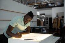 Seitenansicht eines jungen afrikanisch-amerikanischen männlichen Modestudenten, der in einem Atelier der Modehochschule an einer Designzeichnung auf einem Leuchtkasten arbeitet — Stockfoto