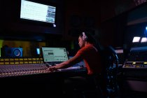 Вид сбоку на молодого инженера-звукооператора смешанной расы, сидящего и работающего за столом для микширования в студии звукозаписи с помощью компьютера и в наушниках — стоковое фото