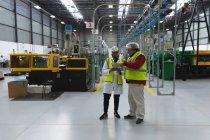 Передній погляд середнього віку Кавказька жінка і робітник на фабриці стоїть в обговоренні, дивлячись на планшетний комп'ютер між рядами обладнання на складі на переробному заводі. — стокове фото