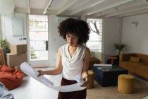 Вид спереди на молодую женщину смешанной расы, стоящую и проверяющую архитектурный рисунок в креативном офисе — стоковое фото