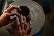 Elevated close up of the hands of a female potter shaping wet clay into a pot shape on a potters wheel in a pottery studio — Stock Photo