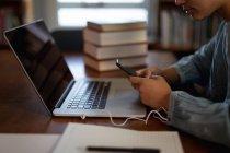Vista lateral de cerca de una joven estudiante asiática usando un teléfono inteligente, una computadora portátil y estudiando en una biblioteca - foto de stock