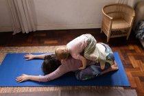 Вид сбоку на молодую кавказскую мать в позе йоги с ребенком наверху — стоковое фото