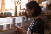Side view close up of a young Caucasian female potter using a smartphone in a pottery studio — Stock Photo