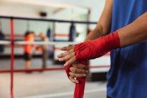 Бічний вид боксера в боксерському кільці обгортає руки, а інший юнак бокс на задньому плані. — стокове фото