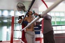 Вид сбоку на молодого боксера смешанной расы, стоящего на ринге, в то время как тренер среднего возраста белый мужчина дает ему воду — стоковое фото