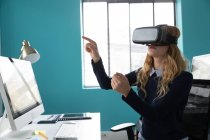 Side view of a young Caucasian woman sitting at a desk wearing a VR headset and with one hand raised and finger pointing in the modern office of a creative business — стокове фото