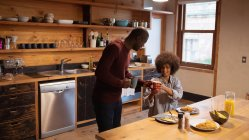 Side view of a young African American man standing and talking as he passes a cup of coffee to his partner, a smiling young mixed race woman sitting at their kitchen table and eating at home — Stock Photo
